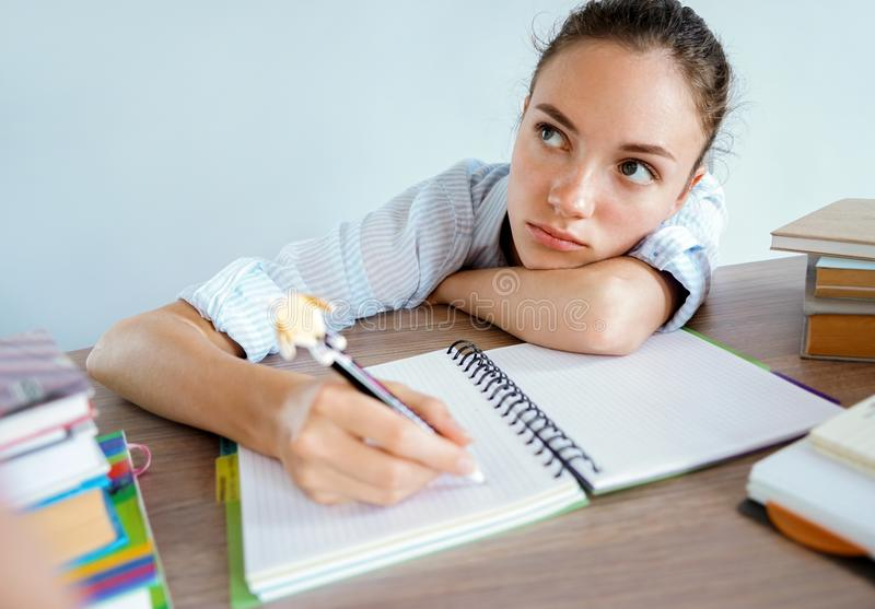 Thinking student writes an essay. stock photography