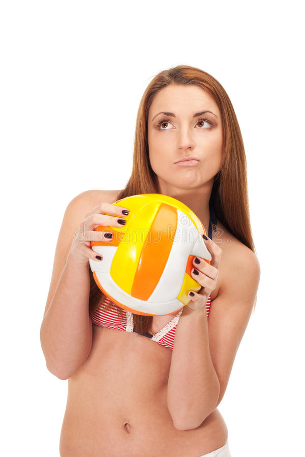 Thinking of summer. Young girl in swimwear is holding deflated ball for volleyball and thinking of coming summer royalty free stock photography