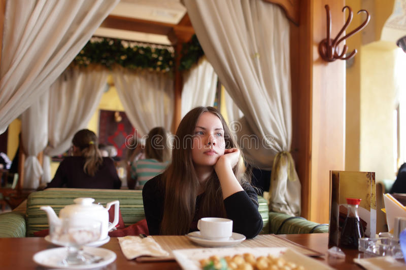 Thinking teen in the restaurant. Portrait of thinking teen in the restaurant royalty free stock photo
