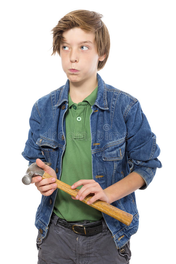 Thinking teenage boy holding a hammer in his hands royalty free stock image