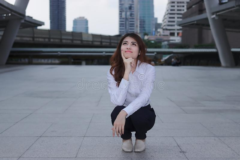 Thinking and thoughtful business concept. Portrait of attractive young Asian businesswoman looking confident and smile at urban royalty free stock photos