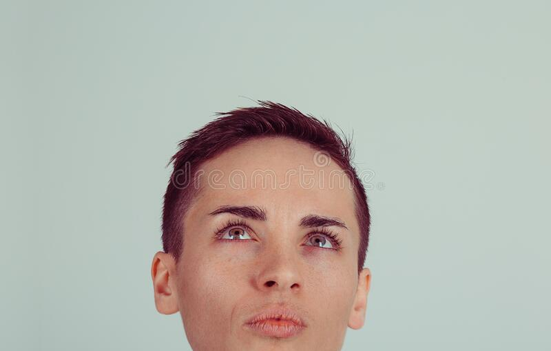 Thinking woman looking up to coy space isolated light green  gray wall background.  stock image