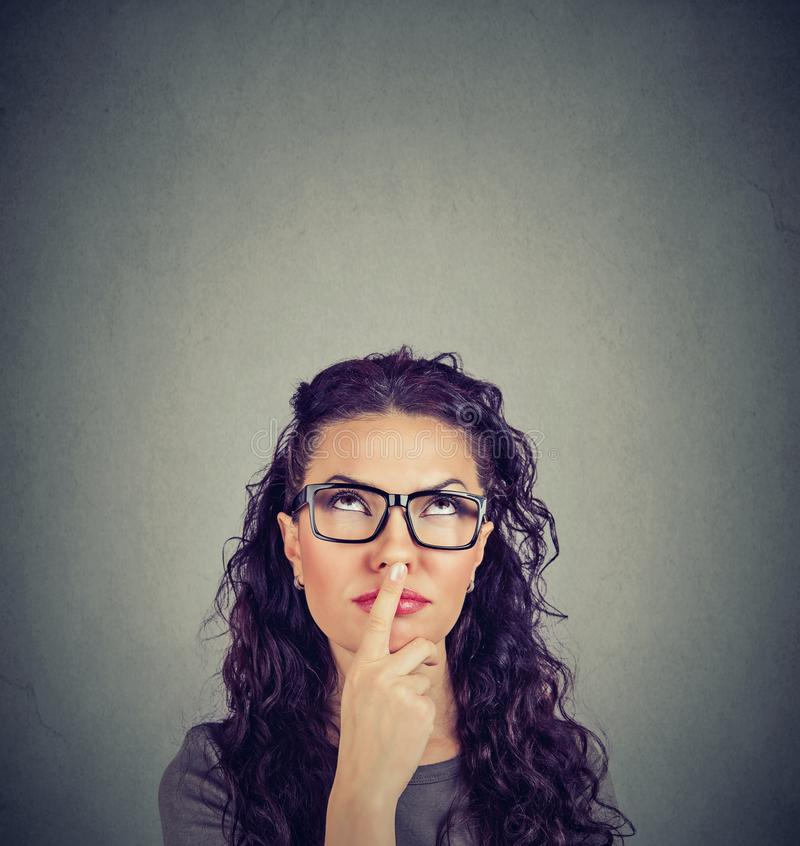 Thinking woman touching lips and looking up stock image