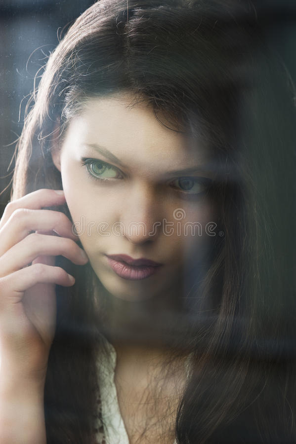 The thinking woman at window potrayed in close-up stock image
