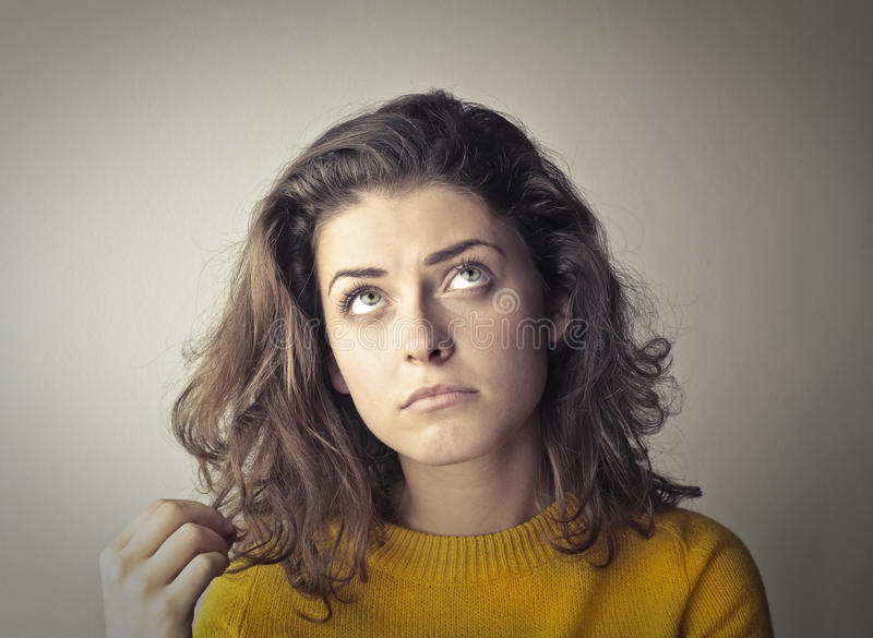 Thinking woman. Woman in yellow shirt thinking royalty free stock photography
