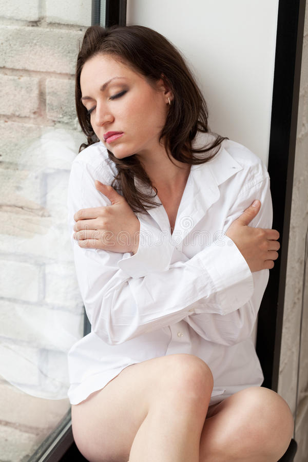 Thinking of you. Girl with eyes closed sitting on windowsill stock photo