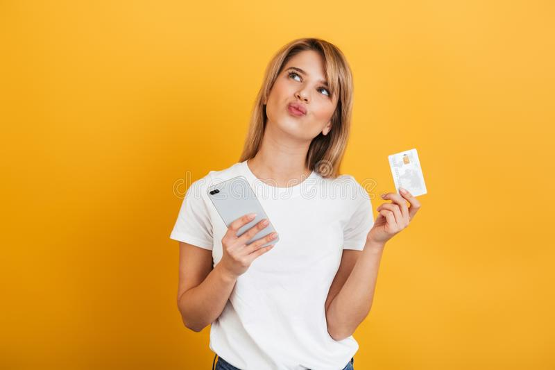 Thinking young blonde woman posing isolated over yellow wall background dressed in white casual t-shirt using mobile phone holding. Photo of a thinking young royalty free stock image