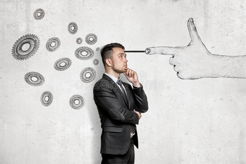 Thinking young businessman with a hand shooting gesture and gear wheels drawn on white wall background royalty free stock photos