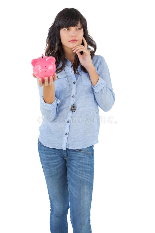 Thinking young woman holding her piggy bank stock photography