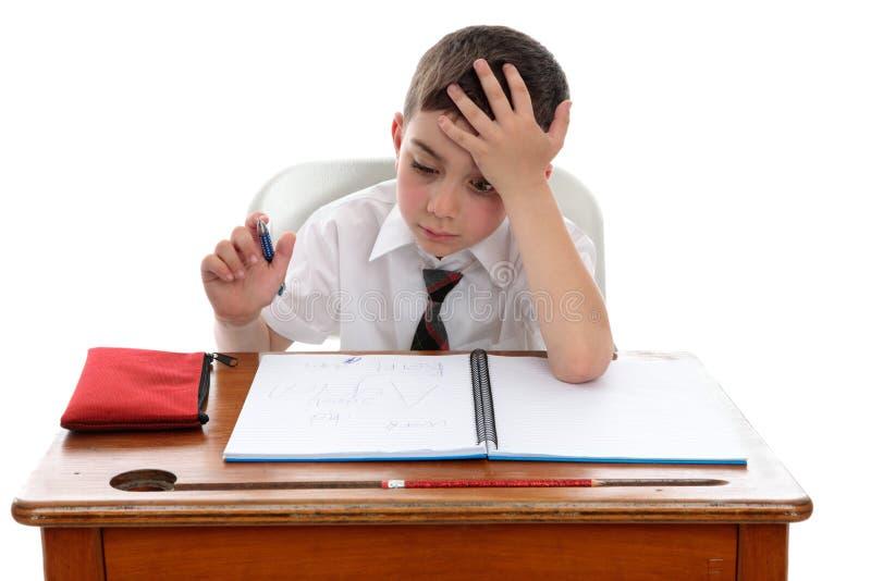 Thinkinhg do menino na mesa da escola imagem de stock royalty free