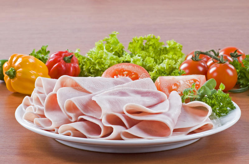 Thinly sliced ham. On a plate, fresh vegetables in the background royalty free stock photos