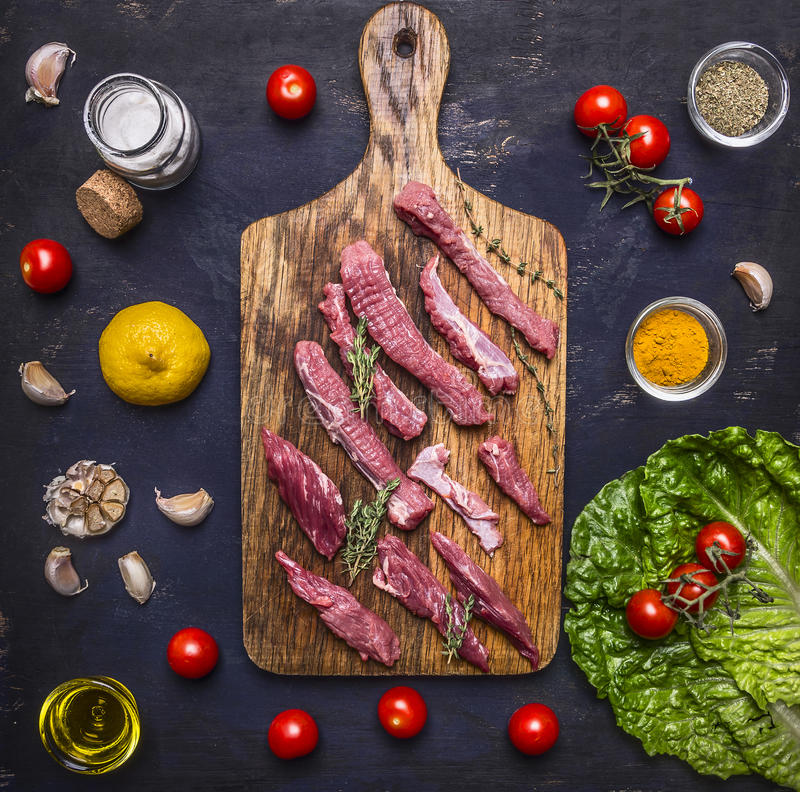 Thinly sliced lamb with garlic on a cutting board with a knife for meat, butter and salt, lettuce on wooden rustic background top royalty free stock photos