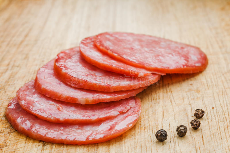 Thinly sliced pieces of salami on a cutting board. stock photo