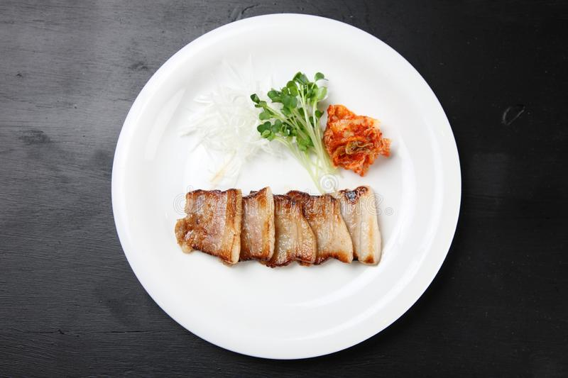 Thinly sliced pork rib saute with kimchi. On a dining table royalty free stock photography