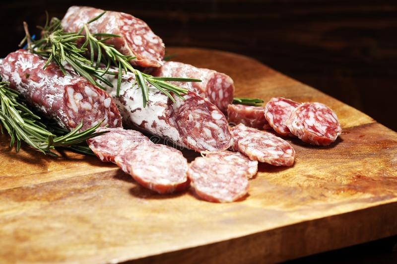 Thinly sliced salami sausages on a wooden texture on the background. Thinly sliced salami on a wooden texture on the background stock image