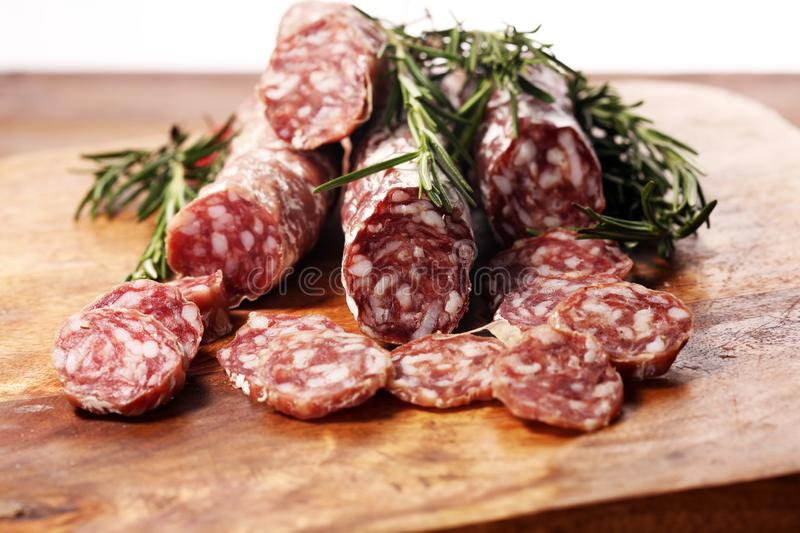 Thinly sliced salami sausages on a wooden texture on the background. Thinly sliced salami on a wooden texture on the background royalty free stock images
