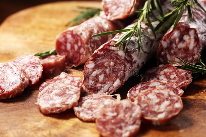 Thinly sliced salami sausages on a wooden texture on the background. Thinly sliced salami on a wooden texture on the background royalty free stock photo