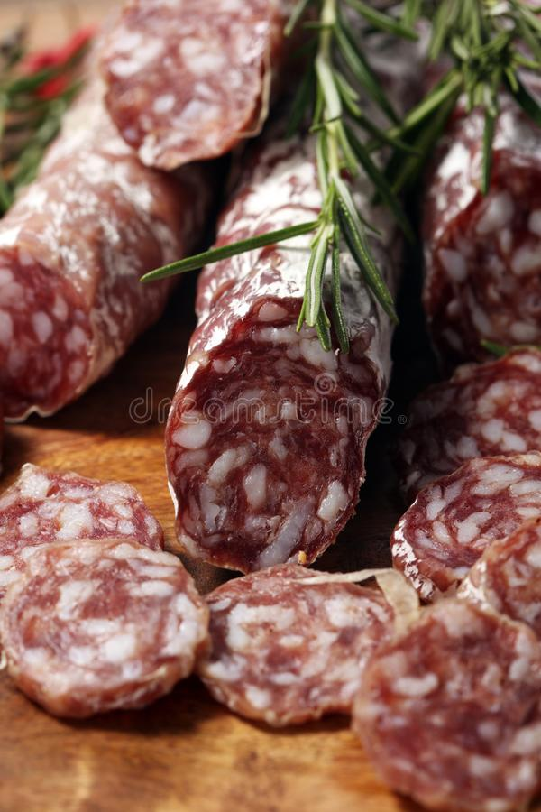 Thinly sliced salami sausages on a wooden texture on the background. Thinly sliced salami on a wooden texture on the background stock images