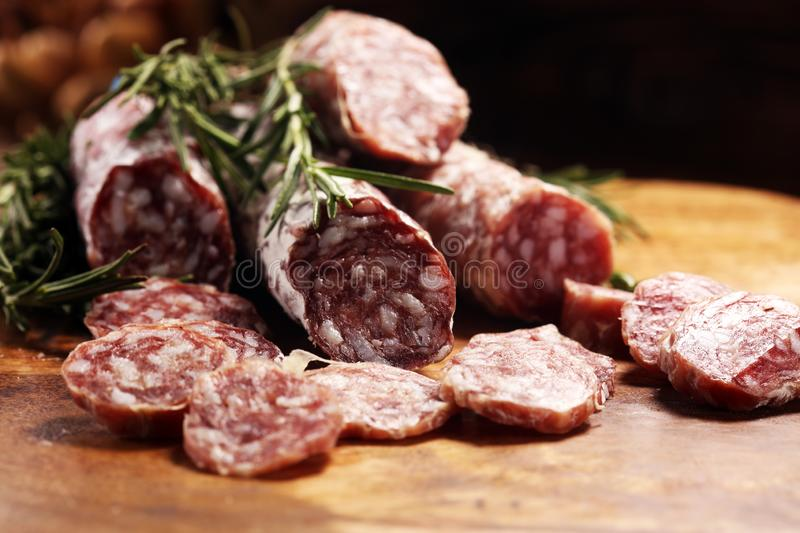 Thinly sliced salami sausages on a wooden texture on the background. Thinly sliced salami on a wooden texture on the background stock photos