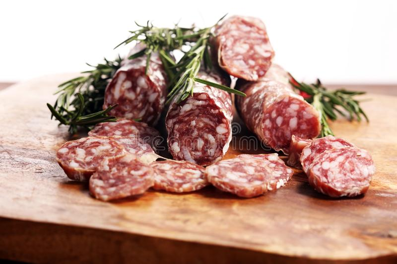 Thinly sliced salami sausages on a wooden texture on the background. Thinly sliced salami on a wooden texture on the background royalty free stock image