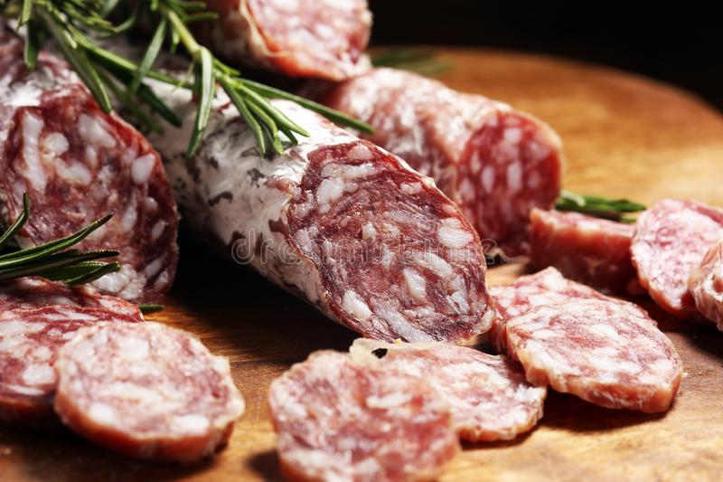 Thinly sliced salami sausages on a wooden texture on the background. Thinly sliced salami on a wooden texture on the background royalty free stock photos