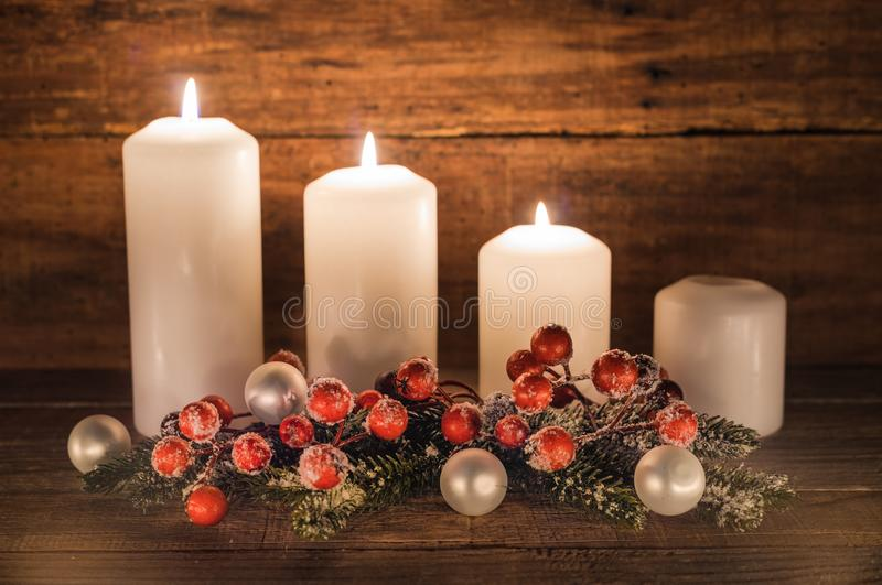 Third Advent. Christmas decoration with christmas bauble, red berries, fir branches and candles for Advent season three candles burning stock photo