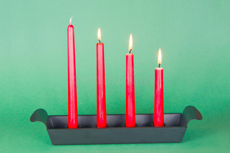Third of Advent with red candles. Candlestick in dark metal with three red candles lighted stock photo