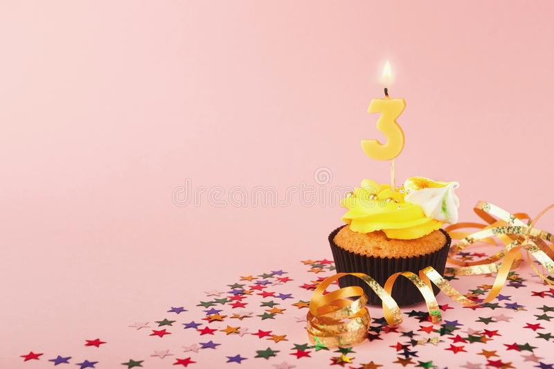 Third birthday cupcake with candle and sprinkles royalty free stock photo