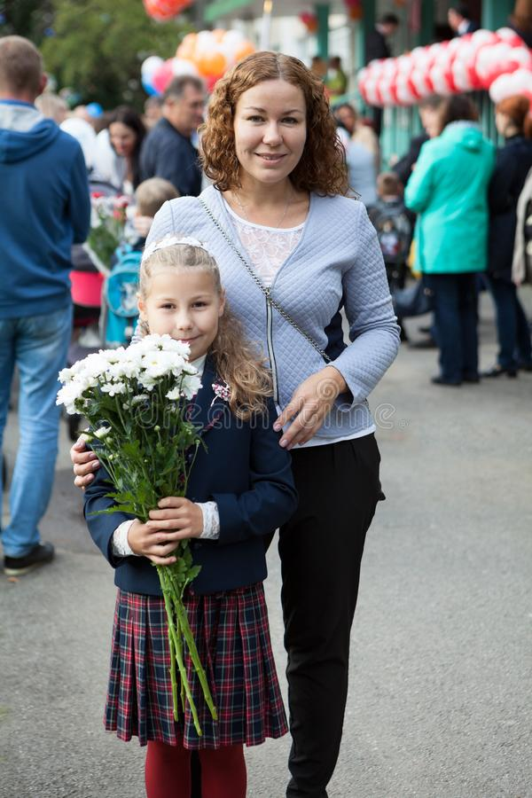 Third-grade girl with bouquet of chamomiles standing in schoolyard with mother, portrait. Third-grade girl with bouquet of chamomiles standing in schoolyard with stock image