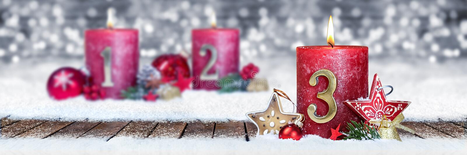 third sunday of advent red candle with golden metal number one on wooden planks in snow front of silver bokeh background stock photo