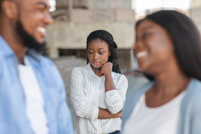 Upset girl jealous to her dating friends, standing alone on background. Third wheel. Upset black girl jealous to her dating friends, standing alone on background stock photography