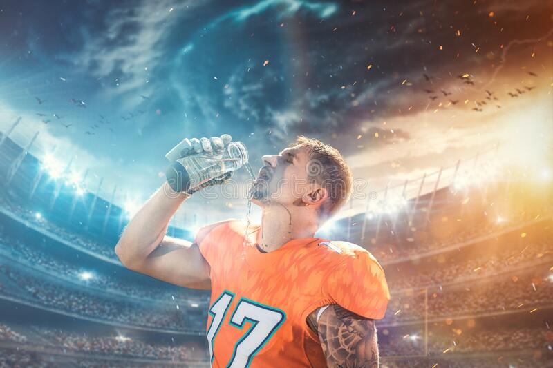 Thirsty American football player in orange jersey drinking water against american football arena royalty free stock photo