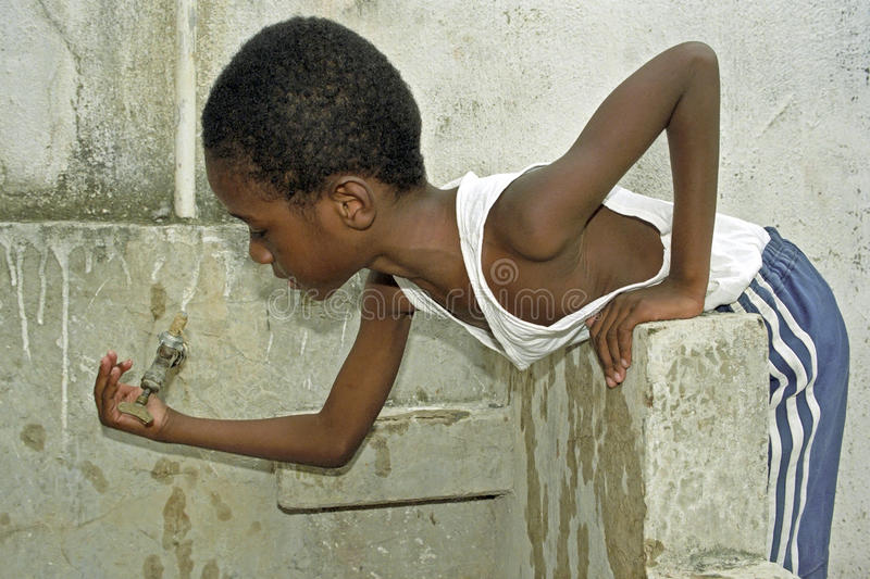 Thirsty Brazilian boy trying to catch water droplets stock photo