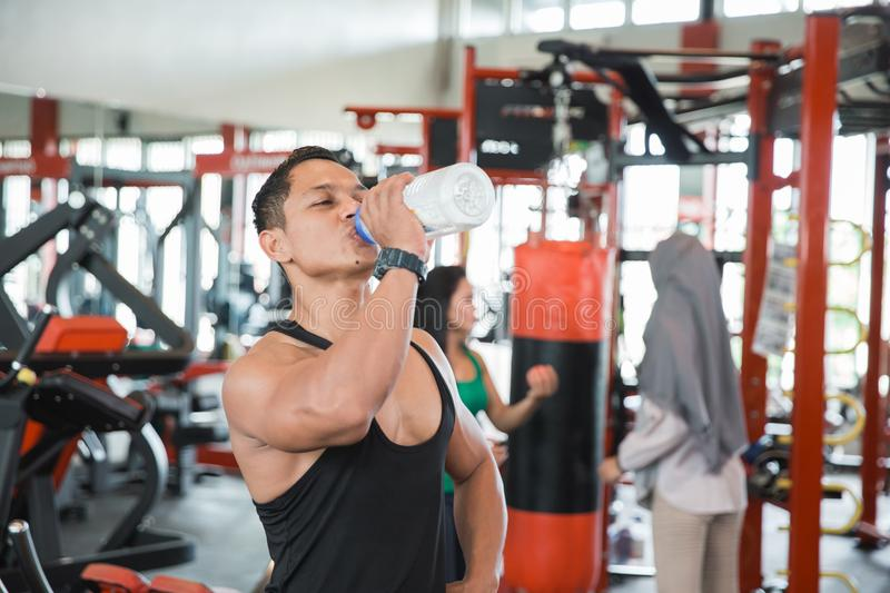 Thirsty healthy asian muscular man royalty free stock image