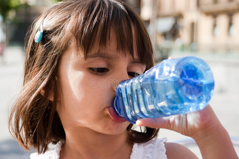 Thirsty little girl drinking water. From a plastic bottle in a summer day. Outdoors stock photos