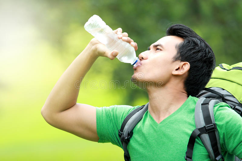 Thirsty man drinking a bottle of water royalty free stock photography