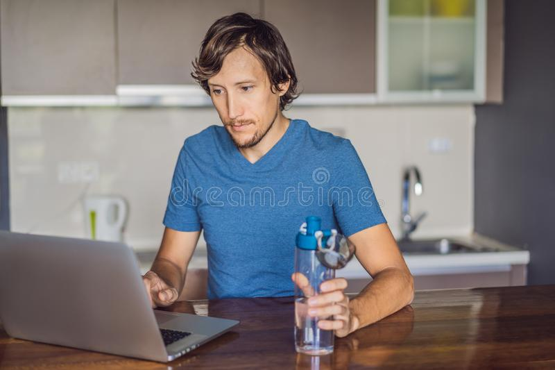 Thirsty man drinks water, uses laptop computer for blogging in networks, watches film, connected to wireless internet stock images