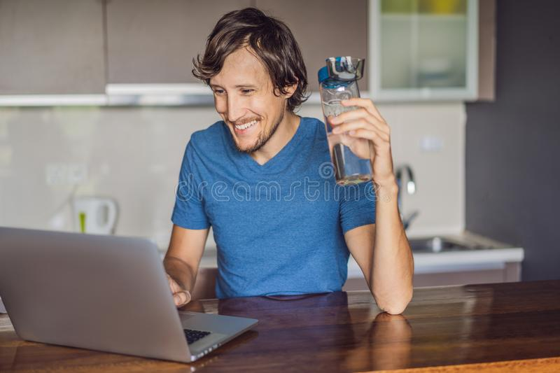 Thirsty man drinks water, uses laptop computer for blogging in networks, watches film, connected to wireless internet royalty free stock photography