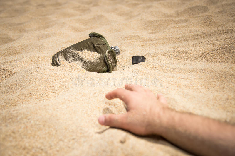 Thirsty man extends his hand to the bottle. Hand of a thirsty person reaches for a water bottle in the desert stock images