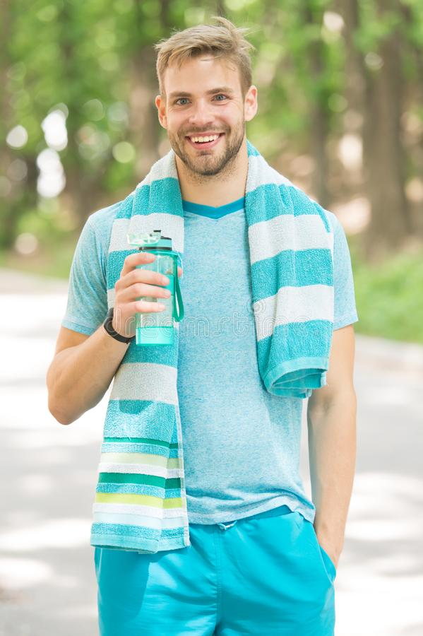 Thirsty after morning jog. Athlete hold bottle care hydration body. Refreshing vitamin drink after great workout. Man. Athletic appearance holds water bottle stock image