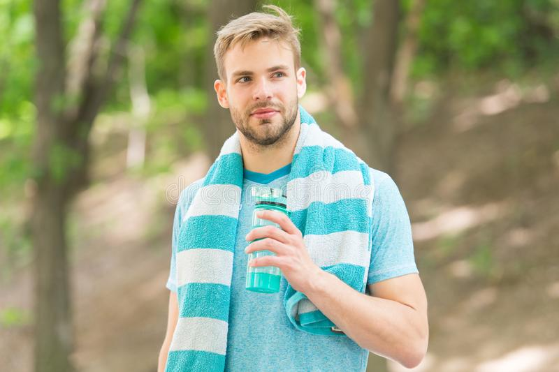 Thirsty after morning jog. Refreshing vitamin drink after great workout. Man athletic appearance holds water bottle. Athlete drink water. Water balance stock photography