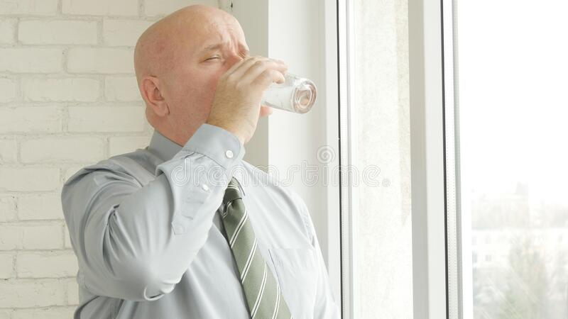 Thirsty Person Drinking Fresh Water from a Glass near Window in Office Room.  stock images