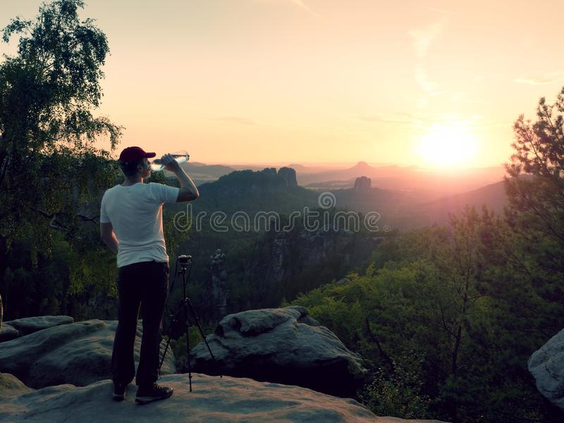Thirsty photograph in black trousers and white t-shirt with bottle of water. Sweaty tired tourist on the peak watching into misty landscape royalty free stock images