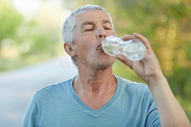 Thirsty senior male drinks water from palstic bottle, being tired after cardio training, has active lifestyle, dressed casually, p. Oses outdoor. Mature man stock photo