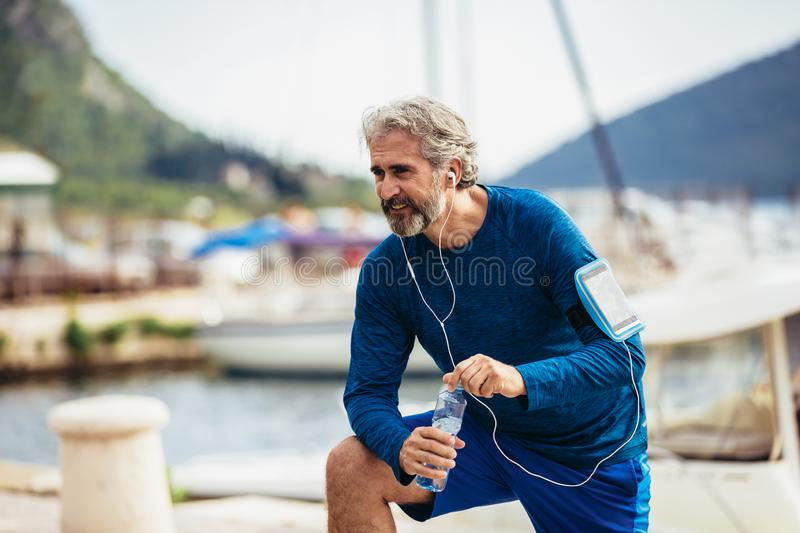 Thirsty senior man drinking water before running. Active old man having a break during his jog routine outside royalty free stock photos