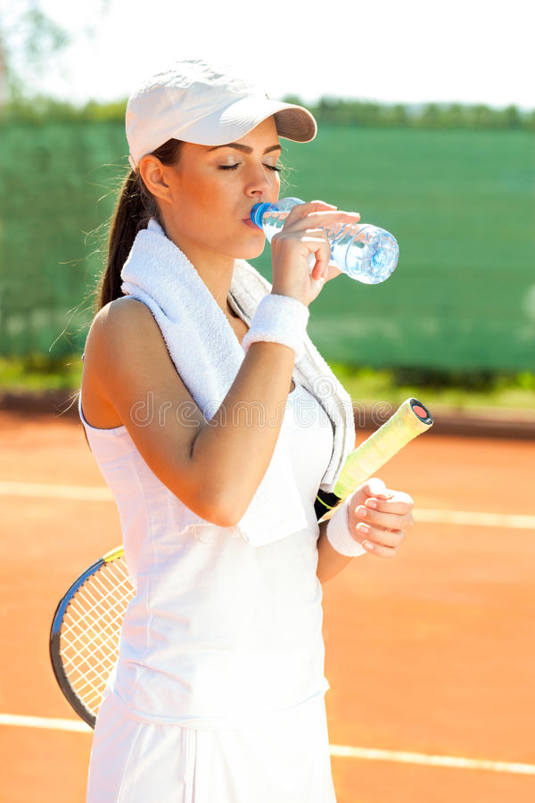 Thirsty sporty woman after tennis training stock images