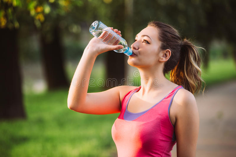 Thirsty woman drinking water to recuperate after jogging royalty free stock photos