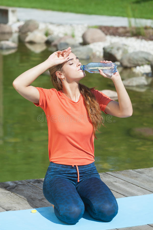 Thirsty after workout. Thirsty attractive woman drinking water after outdoors workout royalty free stock photos