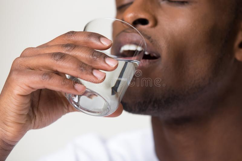 Thirsty young african man holding glass drinking water, closeup view stock photos