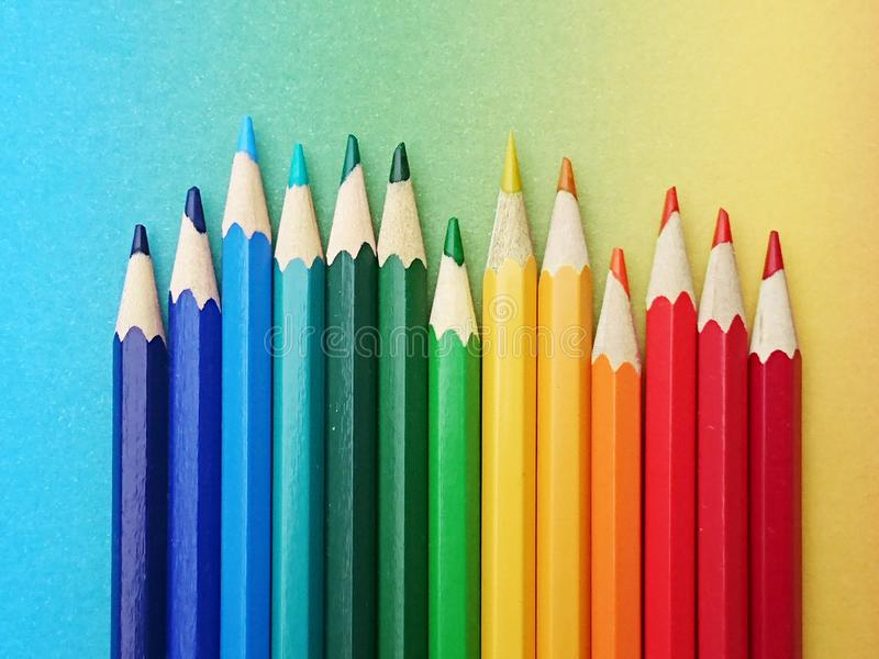 Thirteen colorful pens arranged in the colors of the rainbow on colorful paper in the course of the rainbow. In daylight. the glossy multicolored pencils are stock image